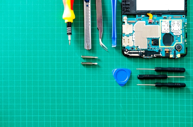 Parts of disassembled gadgets with screw drivers on wooden table