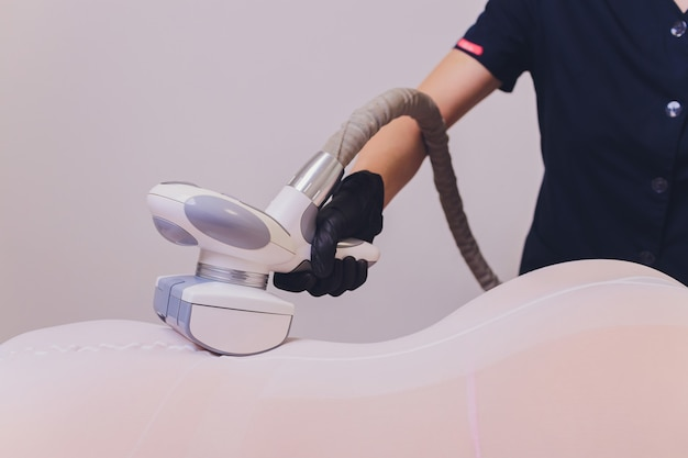 Parts of female body in special white suit having anti cellulite massage.