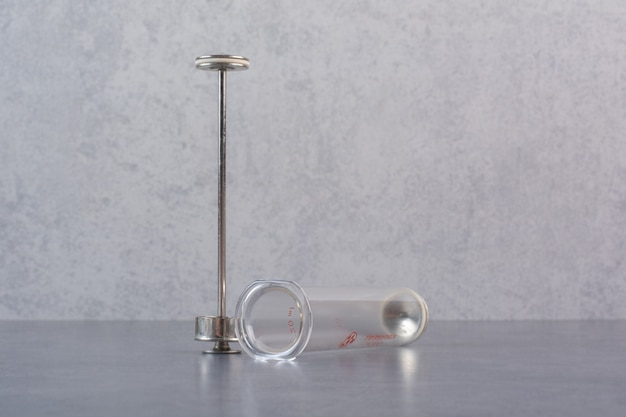 Parts of metal syringe on marble table.