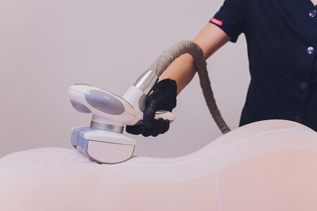 안티 셀룰 라이트 마사지가있는 특별한 흰색 정장을 입은 여성 신체 부위.