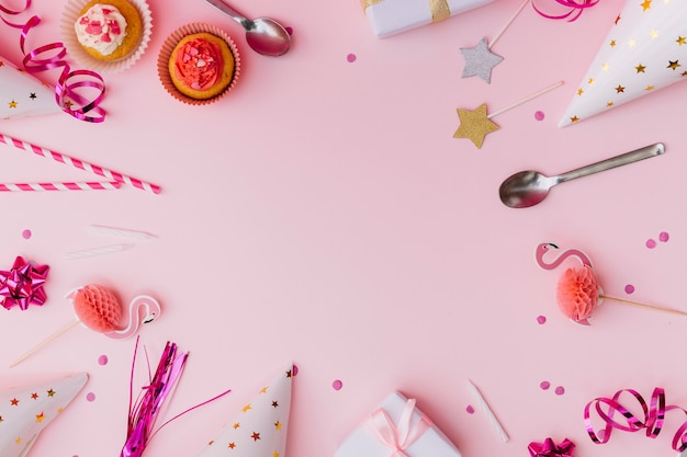 Party accessories with cupcake and spoon over the pink background