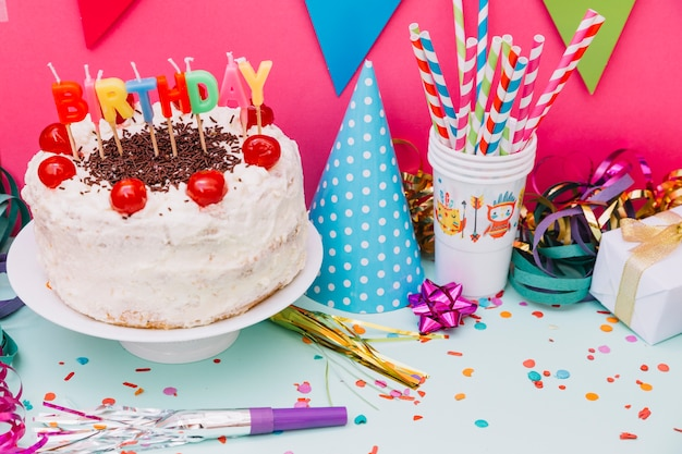 Party accessories with decorated cake on pink and blue background