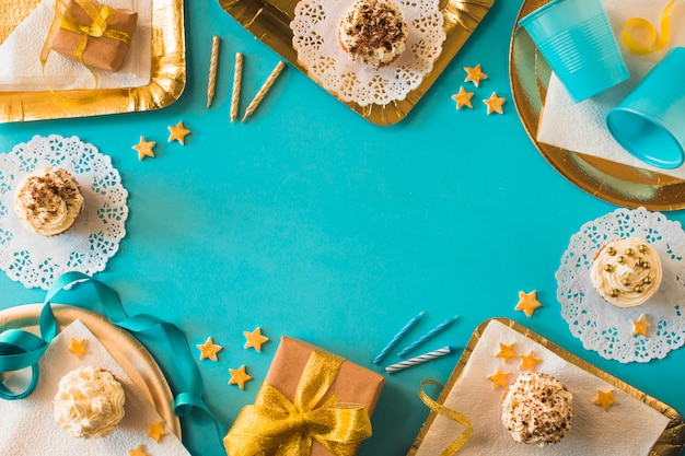 Party accessories with muffins and birthday gifts on turquoise backdrop