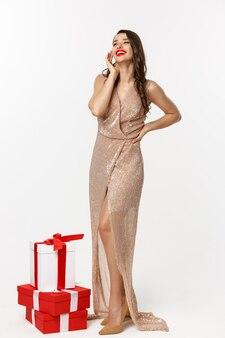 파티 및 축하 개념입니다. 우아한 드레스를 입고 웃고 있는 완벽한 여성의 전신, 크리스마스 선물 근처에 서 있는 흰색 배경