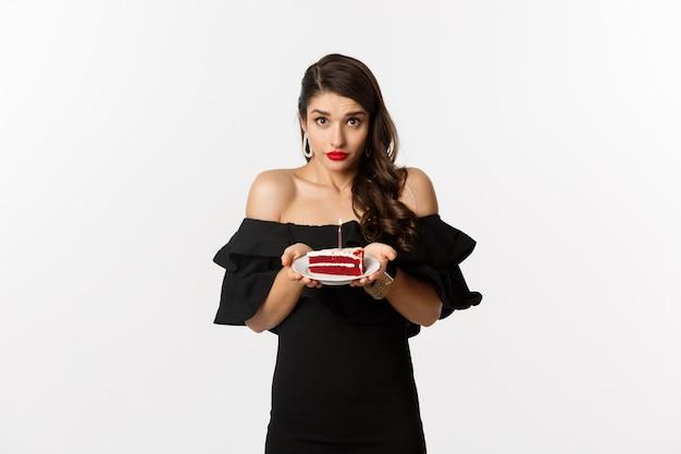 パーティーとお祝い。白い背景の上に立って、b-dayキャンドルで願い事をするように頼んで、あなたにバースデーケーキを与える黒いドレスを着た優しい女性。