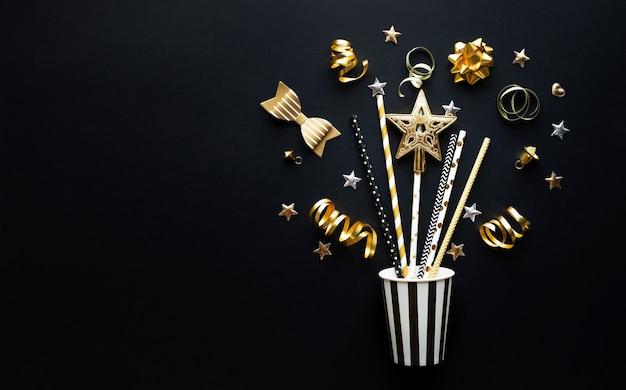 暗い色の背景に金色の小道具と飾りでパーティーやお祝い。フラットレイデザイン