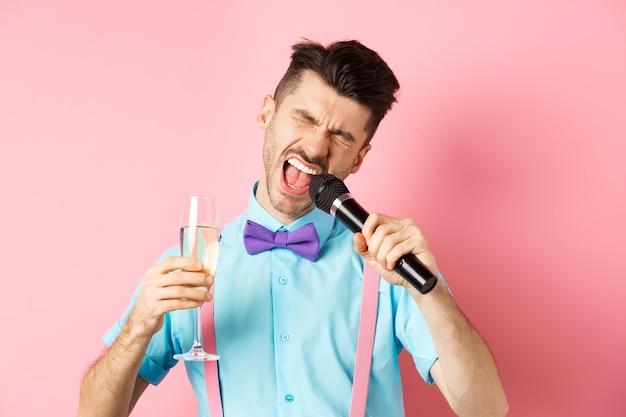 파티 및 축제 이벤트 개념. 마이크에서 노래 하 고 유리에서 샴페인을 마시고, 노래방 바에서 재미, 분홍색 배경에 서있는 술 취한 재미있는 남자.