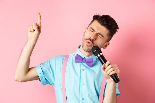 파티 및 축제 이벤트 개념. 마이크에 노래, 분홍색 배경에 서 노래에서 높은 음표에 도달으로 손가락을 올리는 재미 있은 남자.