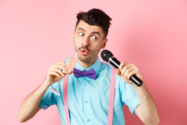파티 및 축제 이벤트 개념. 재미 있은 녀석 노래 노래방, 마이크와 함께 노래를 수행 하 고 분홍색 배경에 서있는 유리에서 샴페인을 마시는.