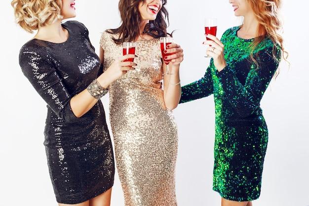 파티 및 휴일 개념. 럭셔리 반짝이 장식 조각을 입은 세 명의 매력적인 여성이 칵테일을 마시고 즐거운 시간을 보냅니다. 할리우드 메이크업, 물결 모양의 헤어 스타일. 흰 바탕.