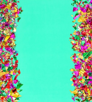 Party background. colorful confetti decoration on neo mint paper texture