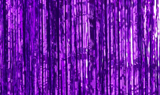 Party background. decor made of purple foil, tinsel and candy.