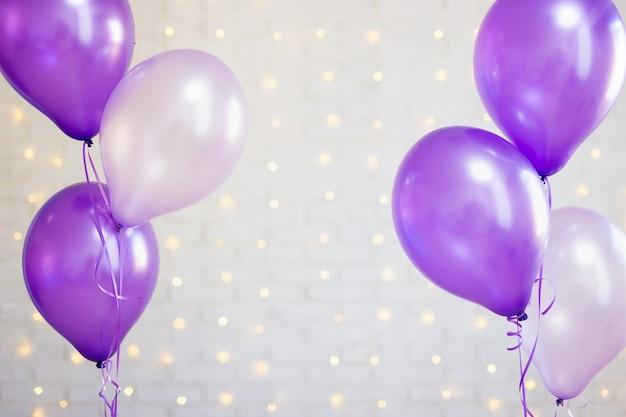 パーティーの背景-ライトと白いレンガの壁の背景の上の紫色の風船