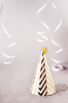 Party background with golden striped cone hat