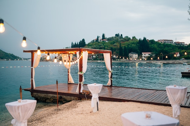 Party on the beach. the pier in the gulf of kotor. a gazebo decorated garlands