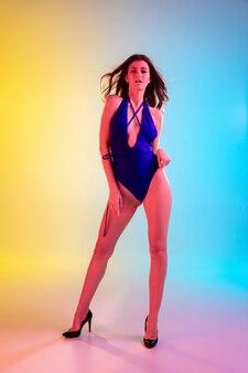 Вечеринка. красивая соблазнительная девушка в модном синем купальнике на градиентном желто-синем фоне в неоновом свете. портрет в полный рост. copyspace для рекламы. лето, мода, красота, концепция эмоций.