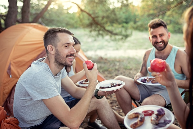 Вечеринка, кемпинг мужской и женской группы в лесу. расслабляющий и едят барбекю на фоне зеленой травы. отпуск, лето, приключения, образ жизни, концепция пикника