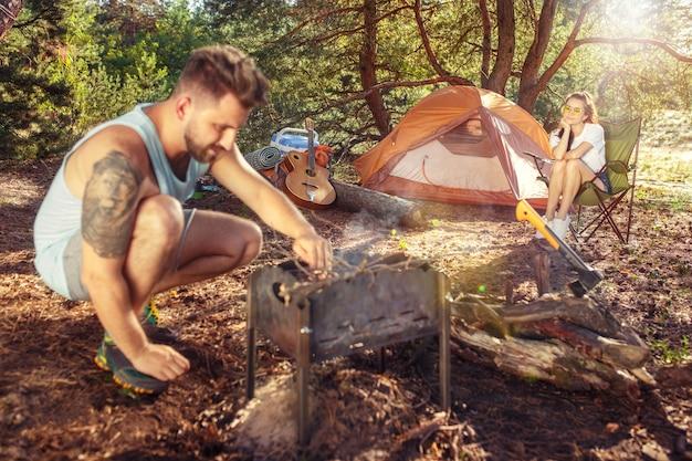 파티, 숲에서 남녀 그룹의 캠핑. 그들은 푸른 잔디에서 휴식을 취합니다. 휴가, 여름, 모험, 라이프 스타일, 피크닉 개념
