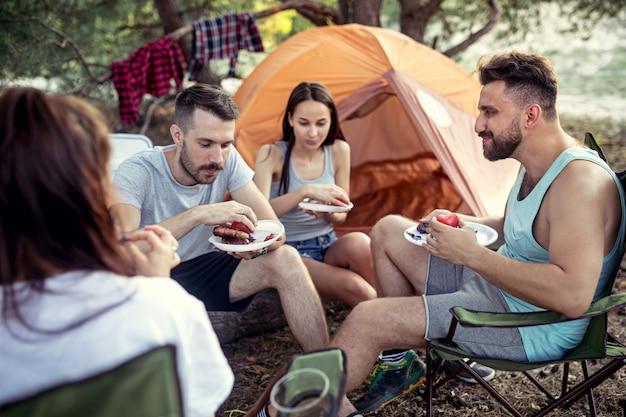 숲에서 남성과 여성 그룹의 파티, 캠핑. 그들은 편안하고 바베큐를 먹는