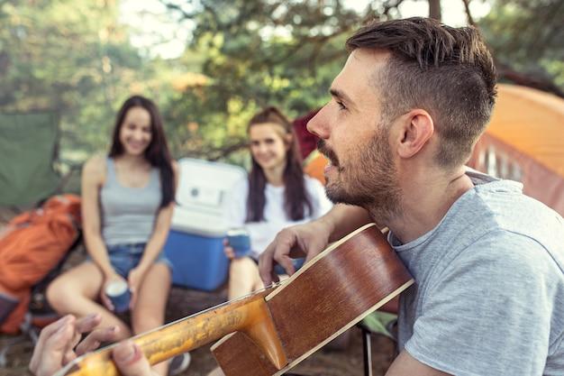 파티, 숲에서 남녀 그룹의 캠핑. 그들은 휴식을 취하고 푸른 잔디를 배경으로 노래를 부릅니다. 휴가, 여름, 모험, 라이프 스타일, 피크닉 개념