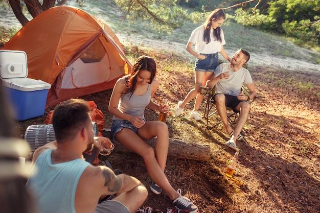 숲에서 남성과 여성 그룹의 파티, 캠핑. 그들은 편안한