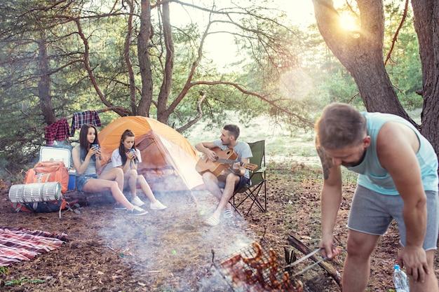 Вечеринка, кемпинг мужской и женской группы в лесу