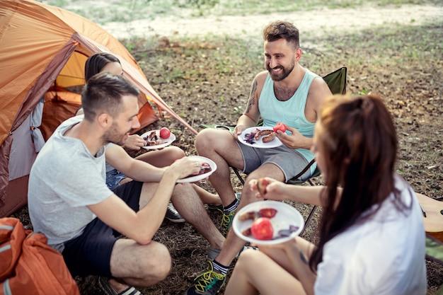 숲에서 남녀 그룹의 파티, 캠핑