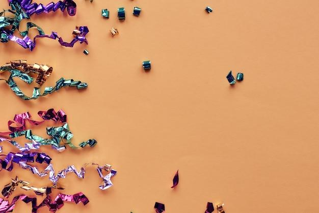 Партия красочные конфетти на пастельном бумажном фоне. блестки, блеск, элементы мишуры новогодняя рамка