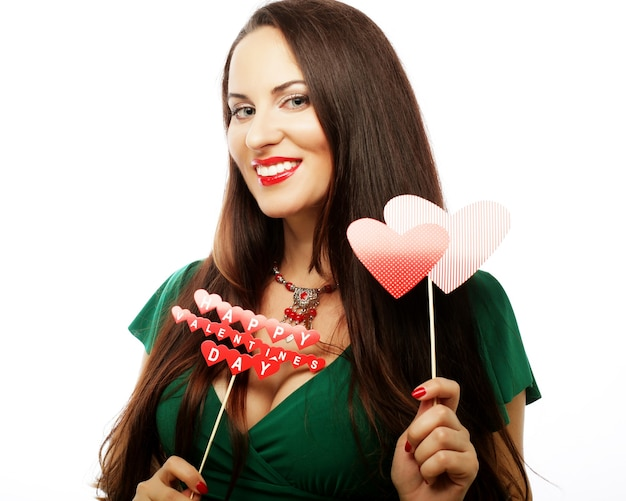 Party concept: young beautiful woman wearing green dress holding paper hearts