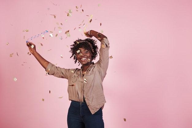 Партийная концепция. бросать конфетти в воздух. афро-американская женщина с розовой предпосылкой позади