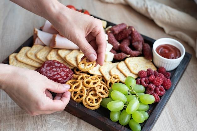 パーティー料理、ソーセージ、フルーツ、クラッカー、チーズを添えたシャルキュトリーボードにミニプレッツェルを置く女性の手。