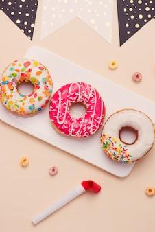 파티. 밝은 색 배경에 다양한 색색의 설탕 둥근 글레이즈드 도넛과 음료수 병.
