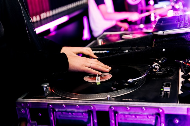 Party dj plays music at hip hop concert.turntables vinyl record player.retro analog audio equipment for disc jockey scratching records.cut tracks with cross fader knob on sound mixer.stage equipment