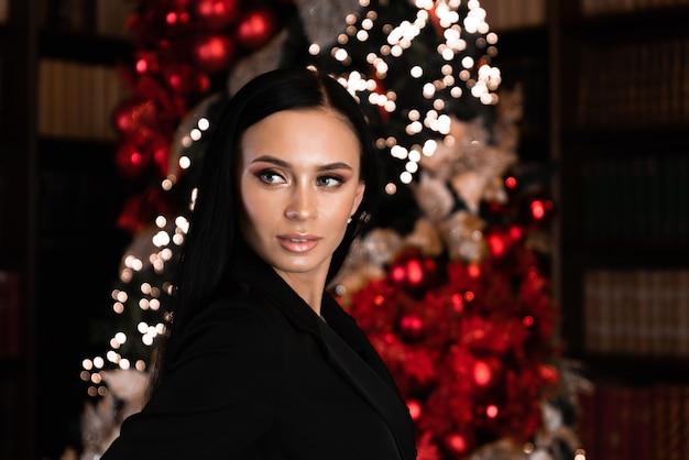パーティーは、クリスマスの上のイブニングドレスの女性と笑顔の休日の人々とお祝いの概念を飲みます
