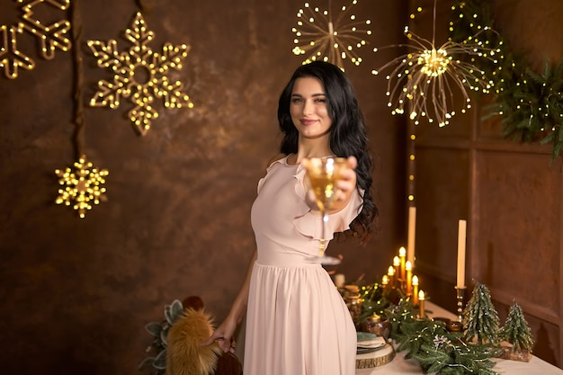Party, drinks, holidays, people and celebration concept - smiling woman in beautiful dress with glass of sparkling wine and champagne over christmas lights background, selective focus