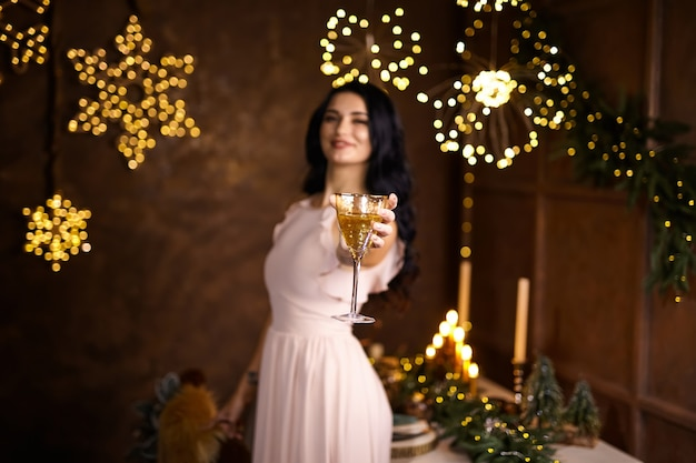 Party, drinks, holidays, people and celebration concept - smiling woman in beautiful dress with glass of sparkling wine and champagne over christmas lights background.