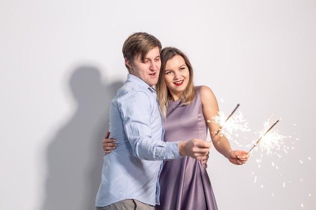 パーティーの家族と休日の概念白い壁に線香花火を保持している若いカップル
