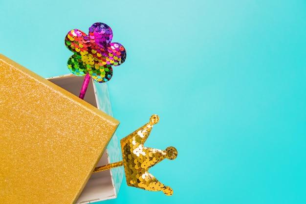 パーティーのお祭りの背景。スパンコールで作られた花と黄金の王冠を持つ魔法の杖。トレンディな休日のコンセプトです。トップビュー、コピースペース