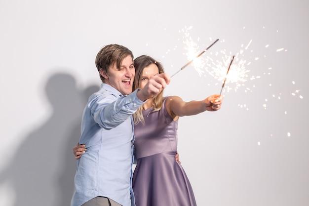 Веселая вечеринка и концепция праздников молодая счастливая пара с бенгальскими огнями на белой стене