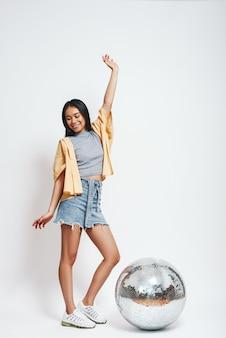 Партийная девушка в полный рост портрет довольно азиатской женщины, стоящей с одной поднятой рукой рядом