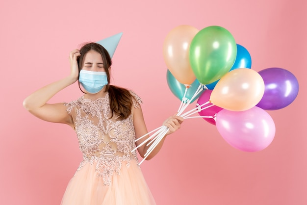 ピンクのカラフルな風船を持って目を閉じるパーティーキャップと医療マスクを持つパーティーの女の子