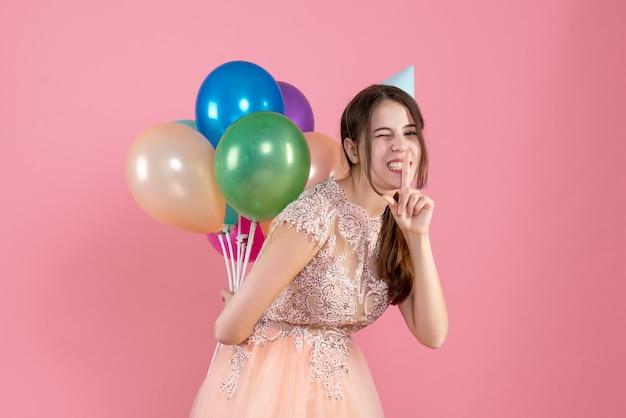 분홍색에 쉿 기호를 만드는 그녀의 뒤에 풍선을 들고 파티 모자와 파티 소녀