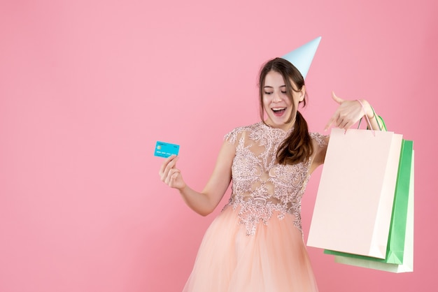 Party girl with party cap holding card and shopping bags on pink