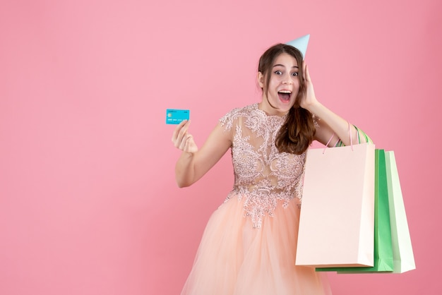 Party girl with party cap holding card and shopping bags putting hand near her cheek on pink