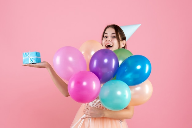 Party girl with party cap holding colorful balloons and gift on pink
