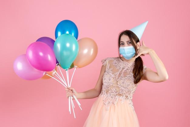 Ragazza festaiola con tappo del partito che tiene palloncini colorati facendo chiamarmi gesto del telefono sul rosa