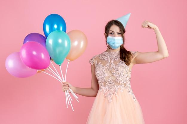 핑크에 근육을 보여주는 다채로운 풍선을 들고 파티 모자와 파티 소녀