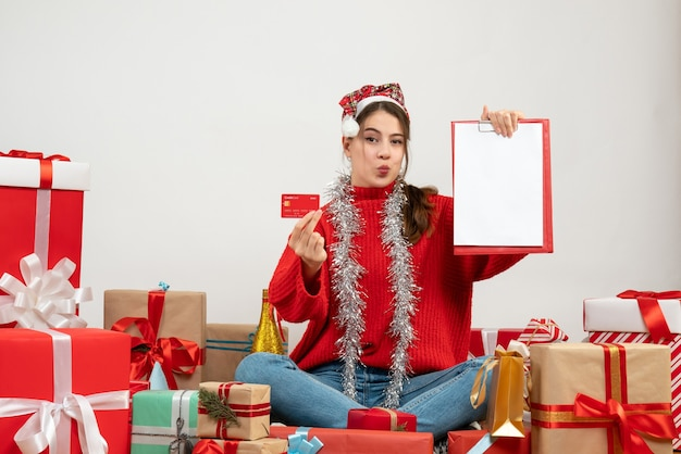 Party girl with santa hat holding card and documents sitting around presents on white