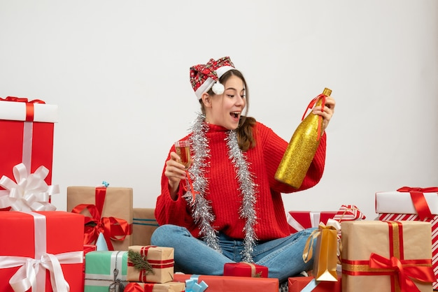 Party girl with santa hat looking at champagne bottle sitting around presents on white