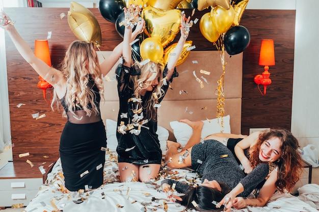 파티 소녀. 재미와 기쁨. 반짝이 색종이. 검은 침대에서 편안한 젊은 여성. 축제 분위기와 장식. 풍선 장식.